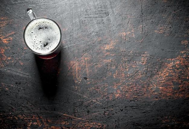 맥주 한잔. 어두운 소박한 배경에