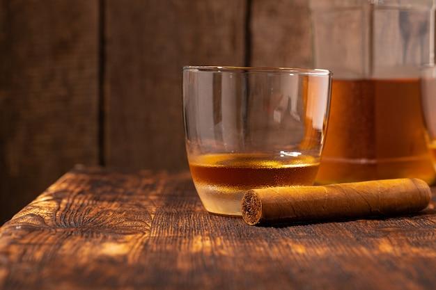 Один стакан виски и сигары на деревянном столе крупным планом