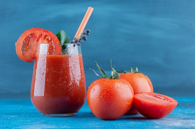 青い背景に1つのガラストマトジュースと2ピースのトマト。高品質の写真