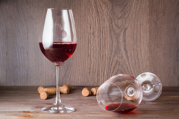 One glass with the remains of red wine is lying, the other is standing filled with red wine and cork on a wooden table