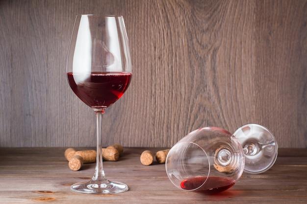 Один стакан с остатками красного вина лежит, другой стоит с красным вином и пробкой на деревянном столе