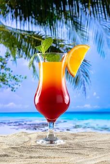 Один бокал с напитком, секс на пляже на песке и пляжный рай на заднем плане