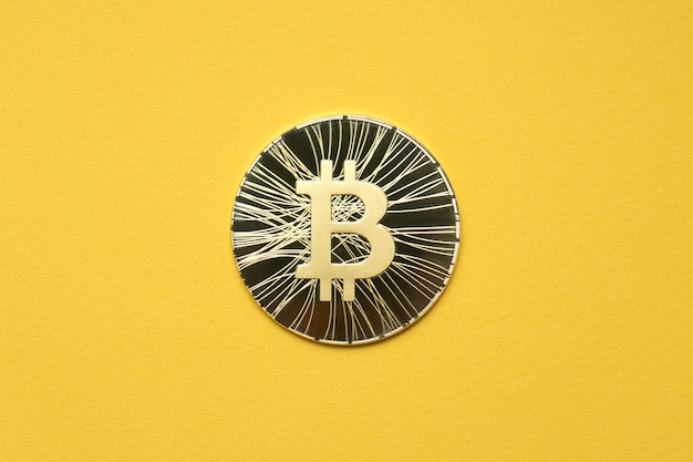 One gold coin bitcoin lies on a yellow background