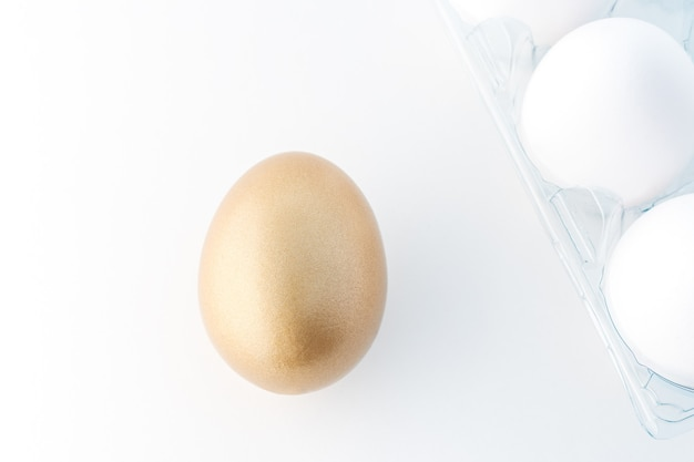 One gold egg and white eggs on white