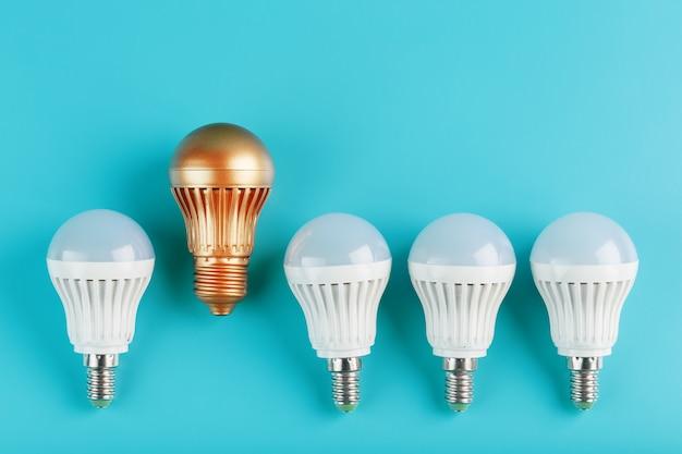 Одна золотая светодиодная лампочка выше и выделяется из ряда белых ламп на синей стене.