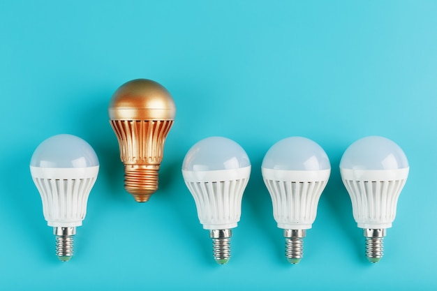 One gold led light bulb is higher and stands out from a row of white lamps on a blue wall.