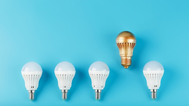 One gold led light bulb is higher and stands out from a row of white lamps on blue.