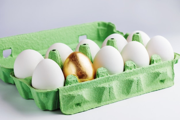 One gold and many ordinary eggs in egg box