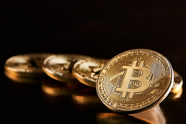 One golden bitcoin as main cryptocurrency in front of other golden bitcoins isolated on balck background.