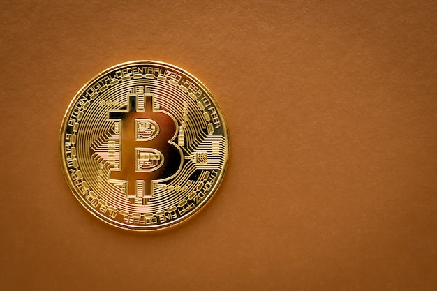One golden bitcoin on brown background. e-commerce, cryptocurrency. blockchain, international mining.