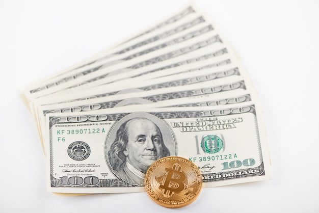 One golden bitcoin compared to stack of hundred dollar banknotes