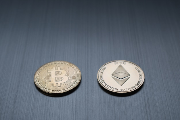 One golden bitcoin and ethereum coin on a metallic background