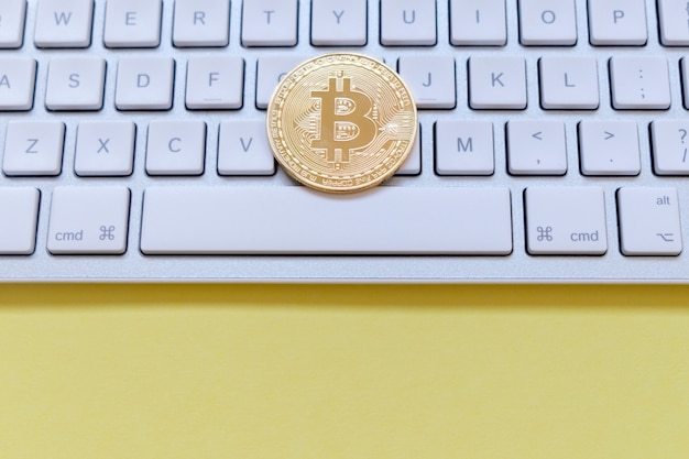 One golden bitcoin on a keyboard. cryptocurrency and business financial concept.