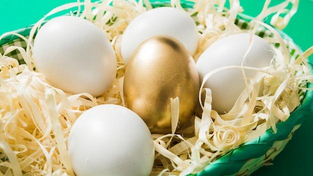 One golden egg among common eggs on wood shaving in the bowl