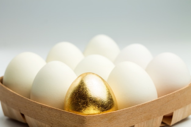 One golden egg among white eggs in a wooden box. uniqueness concept.