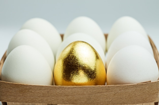 One golden egg among white eggs in a wooden box