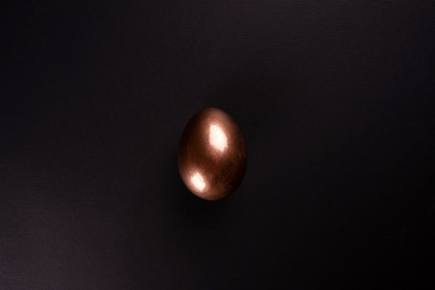 One golden egg lies on a black background, minimalism . flat lay, top view, copy space.