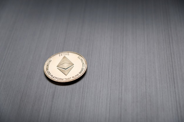 One golden ethereum coin on a metallic. cryptocurrency and business financial concept.