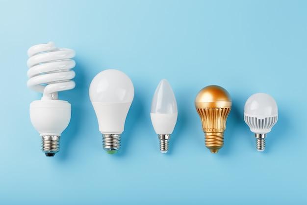 Одна золотая лампочка в ряд энергосберегающих белых ламп на синей стене.