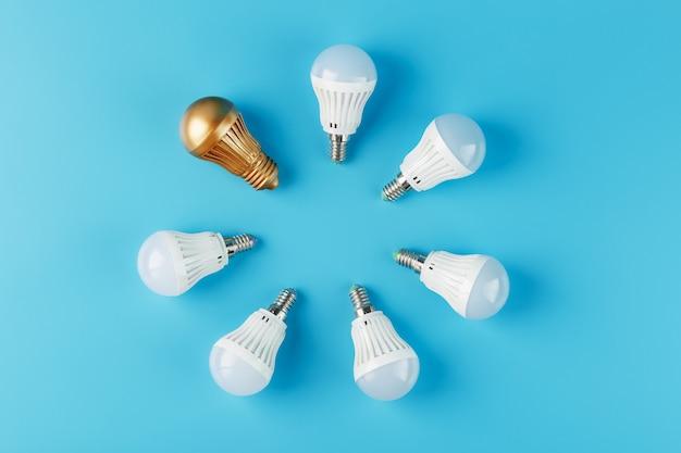 Одна золотая лампочка в кругу кольца энергосберегающих белых ламп на синем.