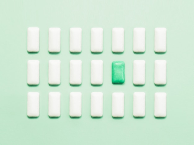 One green chewing gum  standing out of white chewing gums.