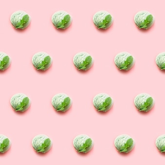 One green pistachio or matcha tea ice cream ball with mint on pink background