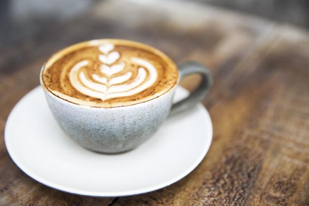 나무 갈색 배경에 아름다운 라떼 아트가 있는 회색 세라믹 컵 카푸치노
