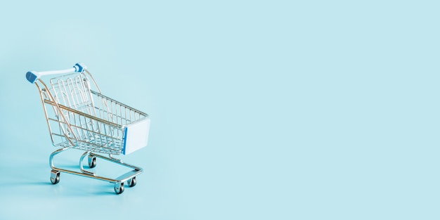 One grocery trolley on pastel blue with space for text.