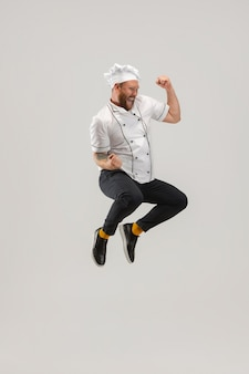 One hadsome bearded man, cook, male chef in white uniform cut cucumber jumping isolated on white