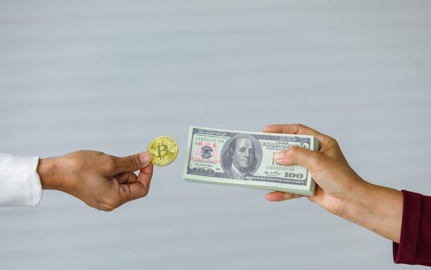 片手で暗号コインを持ち、コピースペースのある厚い紙幣の山と交換する準備ができています。現代人のデジタル資産とビジネスのコンセプト。