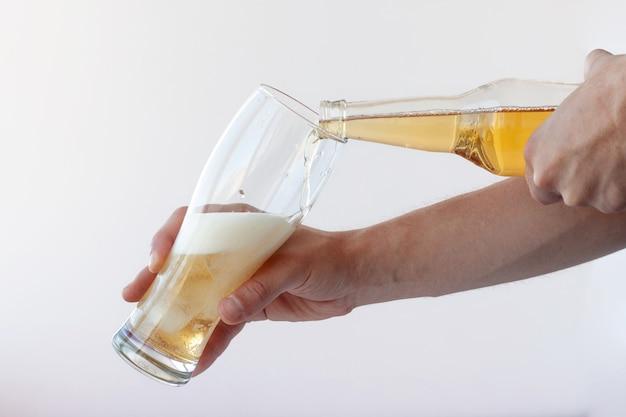 한 손은 비스듬히 얼음이 든 잔을 들고 다른 손은 병에서 가벼운 맥주를 따릅니다.