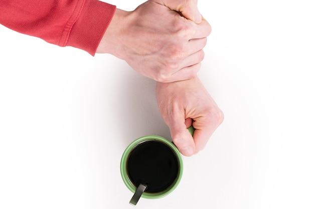 片方の手で緑色のコーヒーを握り、もう片方の手でその腕をつかんで熱い飲み物を飲むのをやめました。