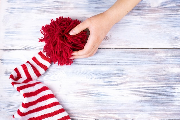 One hand holds a big red pompom of the red striped cap on white wooden table, flat lay, top view.