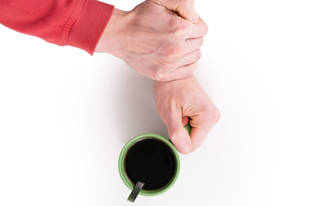 One hand holds a green cup of coffee other hand grabbed that arm to stop drinking hot beverage.