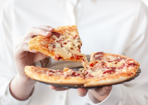 One hand holds a plate of pizza, the other takes one slice on a white background.