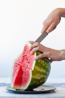 One hand holds ripe red watermelon, other holds knife and cuts off piece of watermelon. vertical frame