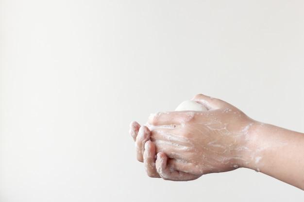 한 손은 위쪽에, 다른 손은 아래쪽에 흰색 배경에 있는 비누 손바닥 사이에 비누를 잡습니다. 질병을 예방하기 위해 손을 씻을 필요가 있다는 개념.
