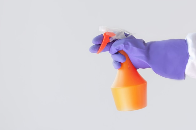One hand in a purple rubber glove holds an orange spray bottle with cleaning agent