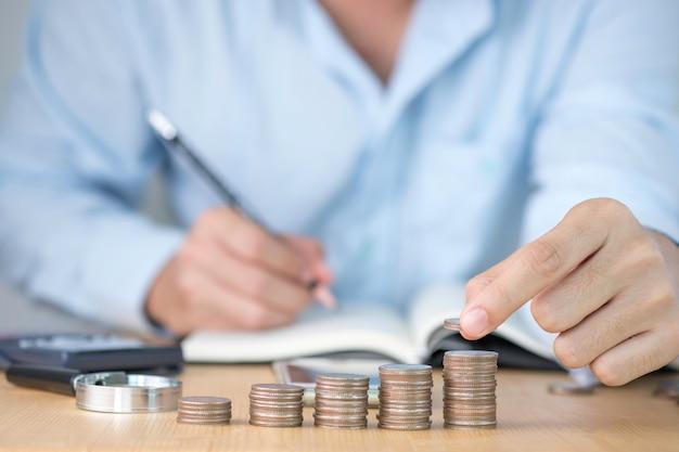 片手でコインを積み、片手で成長ビジネスの記録を書き、投資の概念を保存します。