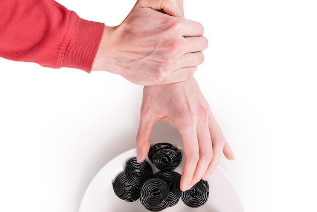 Одна рука берет кусок закрученной спирали лакрицы с тарелки, изолированной на белом фоне