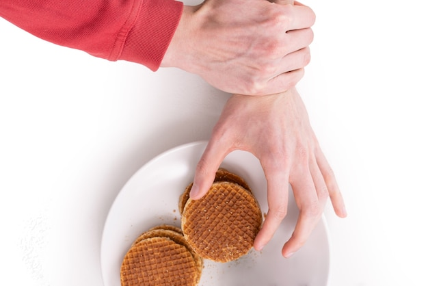 One hand trying to take a cookie from the plate other hand grabbed that arm to stop eating cookies