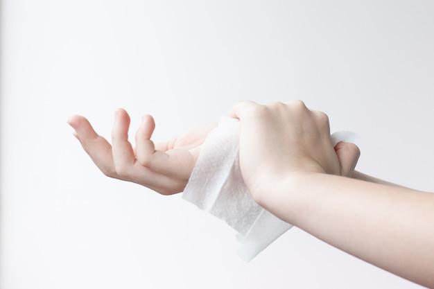 한 손은 밝은 배경에 젖은 항균 천으로 다른 손을 닦습니다.