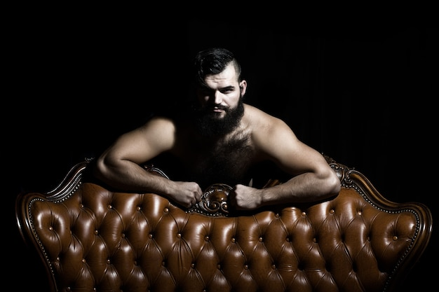 One handsome serious young adult man with long black lush beautiful beard moustache and bare hairy chest near leather couch looking forward indoor on dark background, horizontal picture