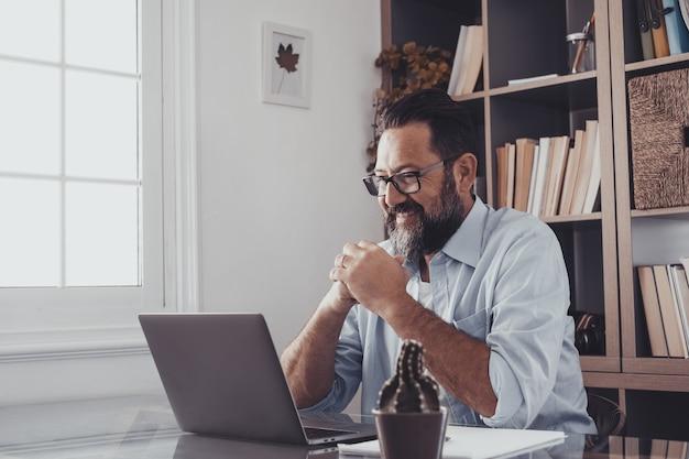 Один счастливый и веселый улыбающийся глядя на ноутбук, работающий дома, в помещении в офисе. довольный мужчина после работы