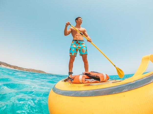 Один счастливый кавказский мужчина наслаждается и веселится в отпуске на открытом воздухе на пляже, катаясь на серфинге с веслом в воде. привлекательный мальчик чувствует себя свободным в путешествии.