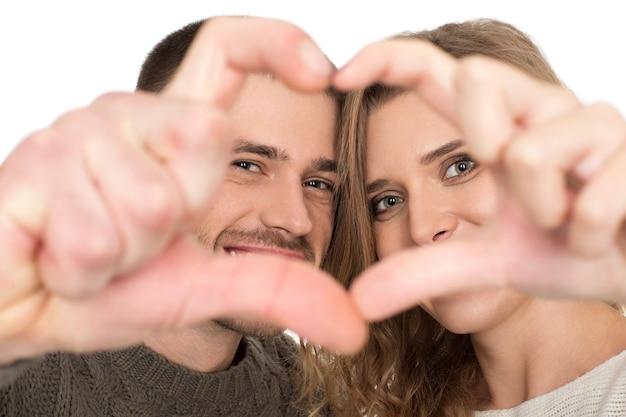 2つの心。彼らの手でハートの形を作る幸せな愛情のあるカップルのトリミングされたクローズアップ