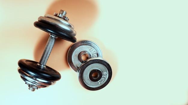 Одна тяжелая гантель для рук и дополнительные отягощения к ней, тяжелый бодибилдинг для тренировок на твердом фоне с градиентом