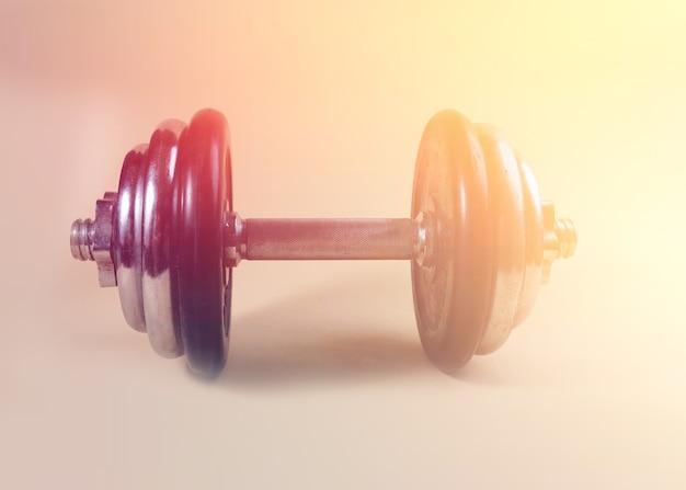 Одна тяжелая гантель для рук, тяжелый бодибилдинг для тренировки на твердом фоне с градиентом