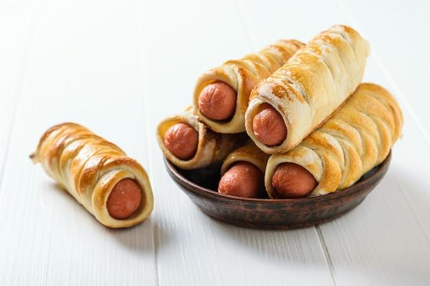 Одна домашняя колбаса в кляре на столе и пять сосисок в глиняной миске на белом деревенском столе