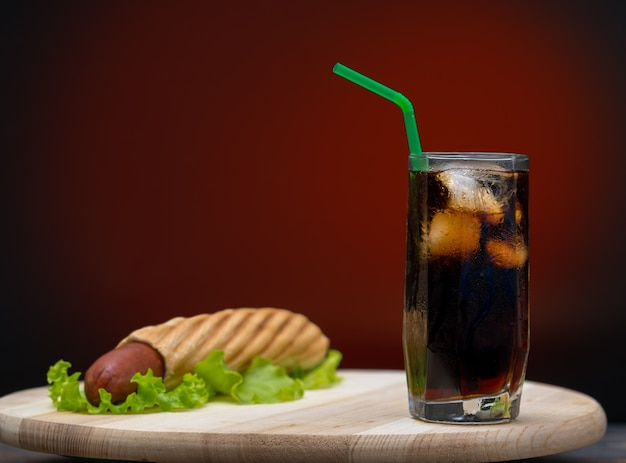 One hot dog stuffed in bread on top of lettuce next to soda glass with ice and straw sitting on white plate